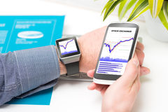 Businessman uses smart watch and phone. Stock Images