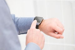 Businessman uses smart watch and phone. Stock Image