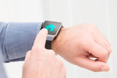 Businessman uses smart watch to home control. Stock Images