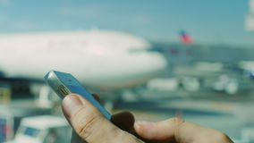 Businessman uses the smartphone at the airport. Hands of a man with the phone in the background of the airfield and stock video