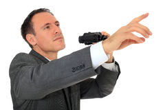 Businessman uses spyglass and points with finger Stock Photos