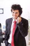 Businessman uses telephon. Businessman in the office uses telephon, smiling and talking Royalty Free Stock Images