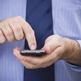 Businessman uses touchscreen smartphone. A businessman operates a touchscreen smartphone Royalty Free Stock Image