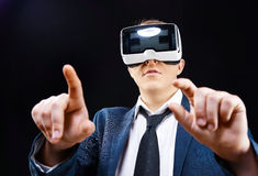 Businessman uses Virtual Realitiy VR head-mounted display. Businessman has fun using his Virtual Realitiy VR glasses head mounted display Royalty Free Stock Image