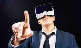 Businessman uses Virtual Reality VR head mounted display. Businessman using his Virtual Reality VR glasses head mounted display Stock Image