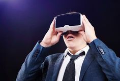 Businessman uses Virtual Reality VR head mounted display. Businessman using his Virtual Reality VR glasses head mounted display Royalty Free Stock Photography