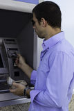 Businessman using ATM Stock Photo
