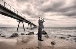 Businessman using binoculars Stock Images