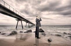 Businessman using binoculars Stock Images