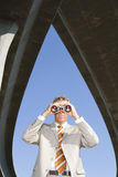 Businessman using binoculars beneath overpasses, low angle view Stock Photography