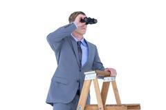 A businessman using binoculars while climbing on a ladder Stock Photos