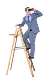 A businessman using binoculars while climbing on a ladder Royalty Free Stock Image