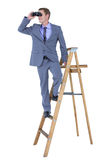 A businessman using binoculars while climbing on a ladder Royalty Free Stock Photography