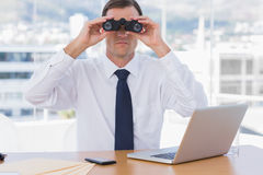 Businessman using binoculars in his office Stock Photos