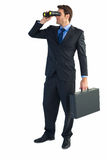 Businessman using binoculars while holding a briefcase Stock Photography