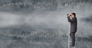 Businessman using binoculars on ladder against upside down city with clouds Stock Photos