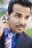 Businessman using bluetooth earpiece. Outside Royalty Free Stock Photos