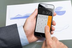 Businessman Using Calculator On Apple iPhone 6 At Table Stock Photos