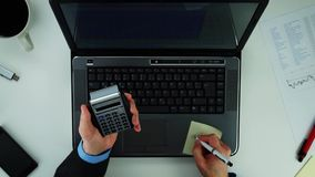Businessman using calculator. Calculator in hands while working on computer stock video