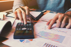 Businessman using calculator and pointing paper chart on desk. Businessman using calculator and pointing paper chart on desk Stock Image