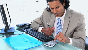 Businessman using a calculator while sitting a his desk. In an office stock video footage
