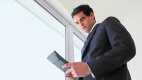 Businessman using a calculator. While standing stock footage