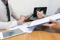 Businessman is using a calculator to calculate the numbers. On wood desk, business finances and accounting concept royalty free stock image