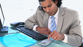 Businessman using a calculator to check numbers on the computer Stock Photos