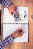 Businessman using calculator while writing on book Royalty Free Stock Images