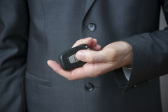 Businessman using car key Stock Images
