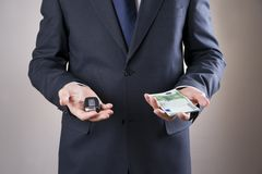 Businessman using car key and money Royalty Free Stock Images