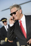 Businessman Using Cell Phone At Airfield. Happy senior businessman using cell phone with airplane captain in the background at airfield Royalty Free Stock Photo