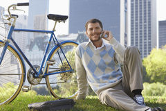 Businessman Using Cell Phone By Bicycle In Park Stock Photography