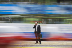 Businessman Using Cell Phone On Busy Street Stock Photo
