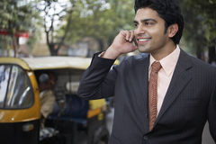 Businessman Using Cell Phone On City Street Royalty Free Stock Image