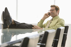 Businessman Using Cell Phone In Conference Room Royalty Free Stock Images