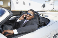 Businessman Using Cell Phone In Convertible. Young businessman using cell phone in convertible near private jet Royalty Free Stock Photo