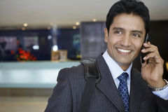 Businessman Using Cell Phone In Hotel Lobby Stock Photo