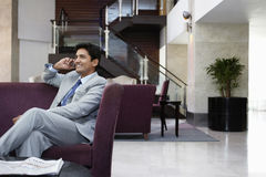 Businessman Using Cell Phone In Hotel Lobby Royalty Free Stock Photo