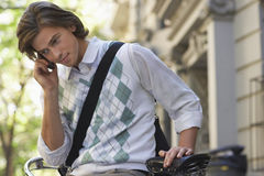 Businessman Using Cell Phone While Sitting On Bicycle Royalty Free Stock Image