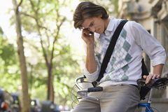 Businessman Using Cell Phone While Sitting On Bicycle Royalty Free Stock Photos