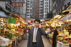 Businessman Using Cell Phone At Street Market Stock Image
