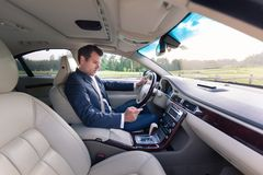 Businessman using cell phone and texting while driving not paying attention to the road. Dangerous texting and driving at the same time royalty free stock images