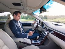 Businessman using cell phone and texting while driving not paying attention to the road. Dangerous texting and driving at the same time Stock Photo