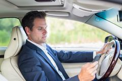 Businessman using cell phone and texting while driving not paying attention to the road. Dangerous texting and driving at the same time stock photos