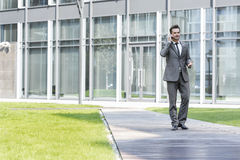 Businessman using cell phone while walking on path outside office Royalty Free Stock Image