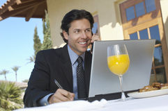 Businessman Using Cell Phone While Writing Notes. Happy businessman using cell phone while writing notes at an outdoor cafe Royalty Free Stock Photo