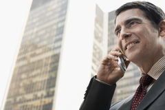Businessman Using Cellphone Against Office Buildings Royalty Free Stock Images