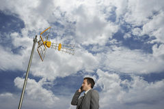 Businessman Using Cellphone Against Satellite Tower And Clouds Stock Photography