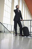Businessman Using Cellphone In Airport. Full length of a businessman using mobile phone in the airport royalty free stock photography